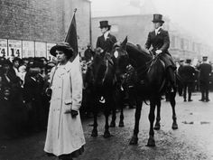A flag carrier and two mounted marshalls (riding astride) in a suffragette march through London in support of the Women's Suffrage Bill, June 1910.