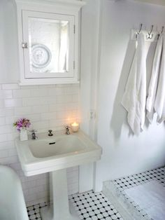 Black and white tile floor, white pedestal sink, white subway tile on wall. Classic and pretty.