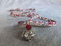 Bola de grossesse avec motif d arabesques, avec un sequin rond, rose / rouge et un en métal argenté, en collier ou sautoir : Collier par bola-de-grossesse