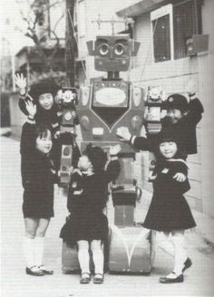 Japanese school children pose with a robot.