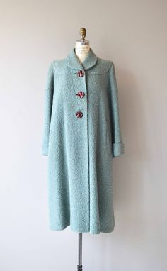 Vintage 1940s muted aqua boucle wool winter coat with rounded collar, three oversized carved resin buttons, wide sleeves with dramatic cuffs, thicker wool lining that zips out of coat (how modern!), tiny metal zip pocket inside the lapel, hip pockets and pink acetate lining.  --- M E A S U R E M E N T S ---  fits like: medium/large shoulder: 17 bust: up to 50 waist: free hip: free sleeve: 24 length: 45 brand/maker: Kam-Ma-Kurl condition: the buttons have discolored the button holes ...