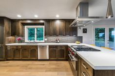 White countertops bring a crisp, fresh feel to this chic kitchen that features streamlined contemporary style and an open layout.