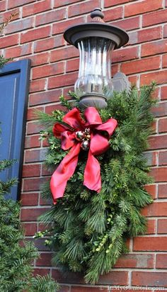 DIY: Christmas Porch Light Decoration - - How to Make and Decorate with Holiday Greenery To Hang Over an Outdoor Light Noel Christmas, Christmas Projects, Winter Christmas, Christmas Lights, Christmas Wreaths, Christmas Greenery, Cheap Christmas, Christmas Ideas, Christmas Picks