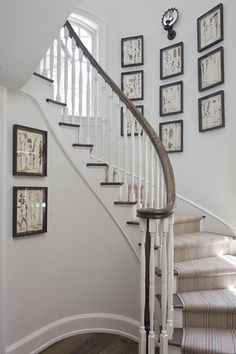 Configuration of artwork on stairwell wall including a sconce. Staircase Railings, Wooden Staircases, Curved Staircase, Banisters, Stairways, Stair Wall Decor, Stairwell Wall, Stairway Walls, Front Hallway