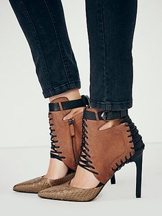 Dolce Vita Wild Hearts Heel at Free People Clothing Boutique:  black stiletto; black lacing at side, front, & back; fulvous leather side panels; taupe scale toe; black ankle belt