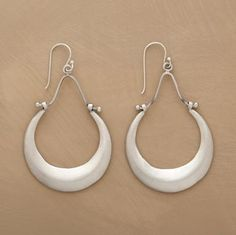 """Ridged hoops of sterling silver brushed to a satiny sheen are hinged by hand to graceful oxbow supports. French wires. 2-1/4""""L."""