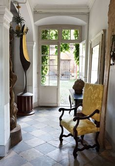 stunning entry - diamond black and white tile, yellow Louis XIV chair, glass paned door, arch above door - Roger Vivier's home in Toulouse, France
