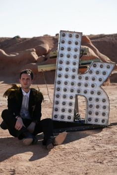 The Killers front-man Brandon Flowers on the set of music video 'Human' in which the band perform in the desert with statement letters that spell the band's name. This pays homage to the band's hometown Las Vegas and the nevada desert which surrounds it.