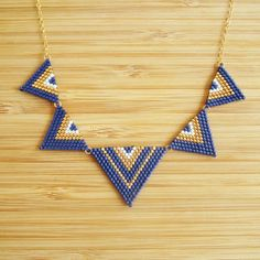Hand woven triangle gold plated bib necklace Navy Blue Miyuki beads, white and gold. Fine gold plated 14 k gold filled chain. Necklace length adjustable through an adjustment chain adorned with a Pearl Swarovski Elements. Bead Jewellery, Seed Bead Jewelry, Seed Beads, Beaded Jewelry, Beading Projects, Beading Tutorials, Seed Bead Necklace, Beaded Earrings, Peyote Patterns