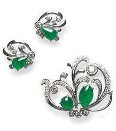 A SET OF JADEITE AND DIAMOND JEWELLERY  Comprising a stylised butterfly brooch, the circular-cut diamond scrolled wing of openwork design, set with a navette and pear-shaped cabochon jadeite of translucent emerald green material, enhanced by two diamond collets, to the diamond collet body; and a pair of earrings en suite, mounted in 18k white gold.