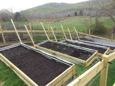 Raised garden beds on a slope. Angled trellis for cucumbers and beans. Gutters to be hung in the back for strawberries