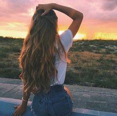 De costas totalmente e com a mão no cabelo