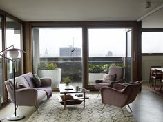 Retrouvius, Barbican, London, living room with view of London - I love the shape of the chairs, the colours and the wonderful Moroccan carpet (brought by Remodelista)