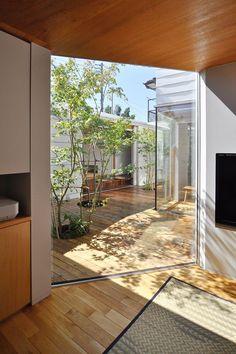 内側の玄関を入って右側の空間から中庭を通して和室を見る。ソファに座ると空がよく見える。