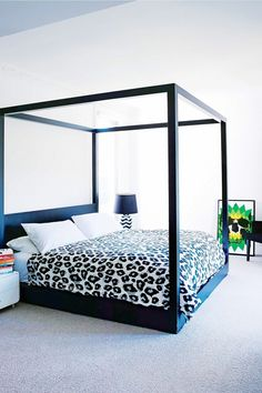 Bedroom with a black canopy bed frame and cheetah bedding