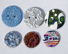 Handmade polymer clay buttons in 2 sizes. The top row of buttons measure 1.5 inches and the bottom row of buttons measure 1 inch across. This is a