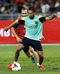 Jordi Allba of Barcelona FC runs with the ball and Andres Inesta chases during Barcelona FC training session at Bukit Jalil National Stadium on August 9, 2013 in Kuala Lumpur, Malaysia.