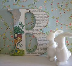 Child's initial covered with a page from a children's book.