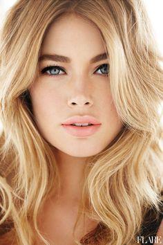 Blonde hair, blue eyes, natural makeup.