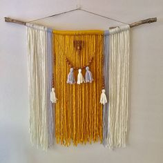 Resting Sun yarn wall hanging This large statement piece has creamy white, light grey and mustard yellow yarn hanging from a natural stick. Grey and white tassels hang from twine with repurposed wooden beads to create a unique feature. This Boho wall hanging has a very warm,