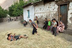 While a group of children look on, one boy shouts out loud to two young boys as they wrestle in some hay outside a family home. The children are all from Yazgulom. About 6,000 people live in Yazgulom, in five different villages. Their language, Yazgulomi, is spoken nowhere else. Yazgulom's residents are Pamiri. The vast majority of Pamiris are Ismaili, but by contrast Yazgulomis practice the Sunni branch of Islam. Photo taken on  July 19, 2011 in Matravn, Yazgulom, Gorno-Badakhshan…