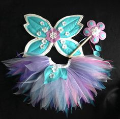 Here is a unique periwinkle fairy, wings, tutu and wand set. These are handmade in the beautiful New Forest in the South of England, a place rich in fairy folk law. The wings are made out of felt with appliqued felt leaves and flower design. The leaves have white swirl stitching detail which does not […]