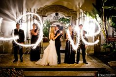 Wedding Photography: Wedding party spelling LOVE with sparklers during wedding at night