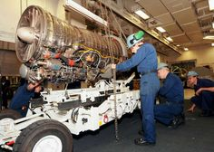 Sailors assigned to USS George H.W. Bush (CVN 77) lower a jet engine onto an engine transport shuttle. - PICRYL Public Domain Image