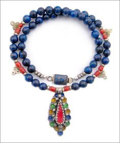 Think Morocco! Beautiful necklace of lapis lazuli, silver and natural coral beads with a handcrafted sterling silver and lapis lazuli clasp. The handcrafted Moroccan Amazigh pendant is sterling silver and enamel. The necklace measures 16 inches in length. The lapis beads are 8 mm in diameter. $229.