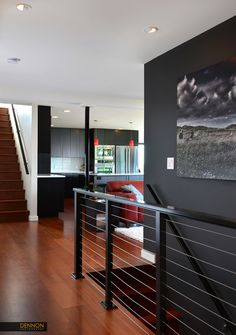 New entry and stair with stainless steel cable railing. The grey wall of the entryway creates a dramatic effect. Views open up into the kitchen and sitting area. Photo by Dennon Photography Design by H2D Architecture and design