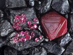 Rubies shine red against black rocks. Ruby, the common name for the mineral corundum in its red form, is a precious gemstone. If the mineral has a blue color it's known as a sapphire. Made up of the elements aluminum and oxygen, corundum also can be yellow, gray or brown.