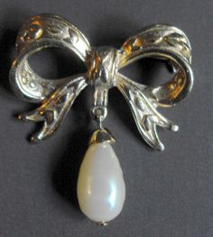B7493 £SOLD (June 2013). A vintage gold tone brooch in the form of a bow with a pearl shaped faux pearl drop.