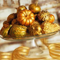 Spray-paint a mix of small gourds shimmery gold, and stack them on a glass cake plate to create an elegant display.