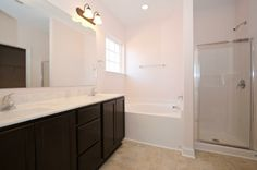 Master suite bathroom with shower, soaking tub, cultured marble dual vanities, and ceramic tile flooring.