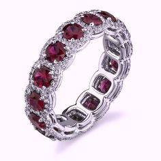 4.46ct Hand crafted 18kt White Gold wedding band features (14) 3.06 cts. round Rubies 3.1mm each, that are each surrounded by diamond halos that total 1.41 cts. Fine quality graded as F/G color and VS
