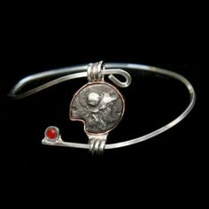 Goddess Bangle Athena by Marcia Fowler-Designs. Athena is the archetype for those who embody the feminine expression of courage and wisdom. Previously to jewelry Marcia worked with bronze sculptures and mosaics. Marcia's new line of work Archetypes combines mythology, metal, and the many facets of being human into wearable art. Each design is a fragment of historical poetry that entices us to acclaim our individuality.