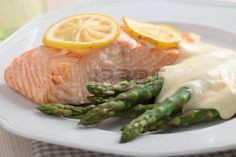 Baked salmon with steamed asparagus under cheese sauce. Shallow DOF