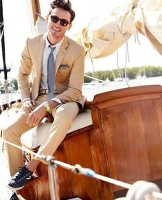Men's White Dress Shirt, Grey Tie, White and Black Gingham Pocket Square, Gold Watch, Tan Suit, and Navy Canvas Low Top Sneakers