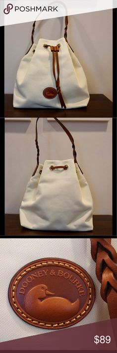 "Dooney & Bourke Leather Nylon Drawstring Purse Excellent like-new condition Dooney & Bourke Nylon/Leather drawstring handbag in pale cream. Guaranteed 100% authentic.   The Nylon Collection combines exceptionally durable fabric with leather trim for accessories that are both functional and lightweight.  H 11.75"" x W 7.5"" x L 11.75"" One inside zip pocket. One inside pocket. Cell phone pocket. Inside key hook. Strap drop length 10"". Lined. Drawstring closure. Dooney & Bourke Bags Shoulder Bags"