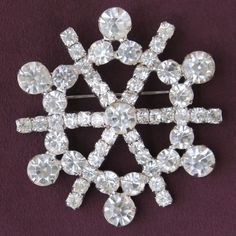 Spoked wheel of clear rhinestones consists of eight rays of small stones rising to a large one in the center, joined by medium stones and alternating with eight more large stones around the edge. Meas