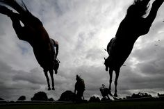 ALAN CROWHURST—GETTY IMAGES Aug. 28, 2014. Runners clear a fence in The £500 Permanent Money Backs Handicap Steeple Chase at Fontwell racecourse in Fontwell, England.