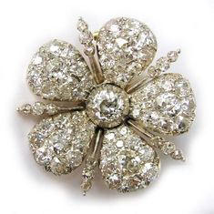A late Victorian diamond brooch/clasp, the brooch in the design of a five-petalled daimond-encrusted flower head with a central old brilliant-cut diamond, the diamonds estimated to weigh a total of 6.25 carats, all cut-down silver collet-set to a yellow gold mount, with detachable brooch and clasp fitting, circa 1890.
