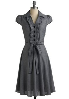 Takes traditional work clothing up a notch with the little details: heart-shaped buttons, waist tie, and ruffles.