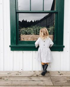 Gazing through the window in a dress with rain boots wanting to g o outside and play in the rain.