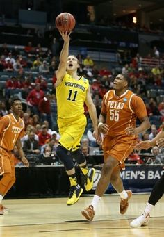 Michigan's Nik Stauskas drives against Texas Cameron Ridley during first half action in their third round NCAA Tournament game Saturday, March 22, 2014 at BMO Harris Bradley Center in Milwaukee Wisconsin.