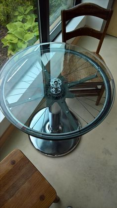 Bike wheel table. Pedestal from Goodwill. Glass top purchased at auction. Peugeot bike wheel donation. Fantastic friend helped assemble.