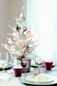 White Christmas: Make a mini tree the focal point of the dinner table. For a simple, dreamy look, use a white artificial tree. Anchor it in a tin pail and adorn with white lights and paper stars or other all-white ornaments.