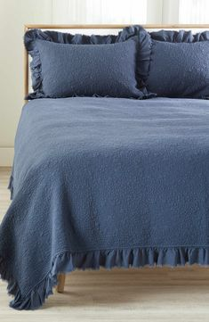 A soft quilt with ruffle trim makes for a vintage-chic addition to your bedroom décor.