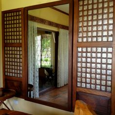 simple, low cost mirror flanked by reclaimed capiz windows.