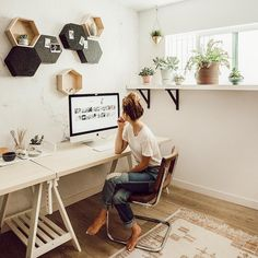Minimalist office ideas with hex shelves and plant ledge at the window. Shared saw-horse desk along the back wall.